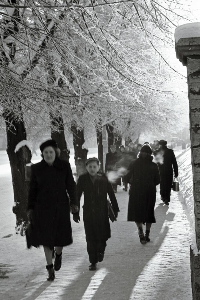 Esiplaanil naine lapsega käest kinni. Inimesed kõnniteel. Foto: Valdur-Peeter Vahi. Detsember 1958.