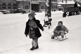 Lapsed talvisel linnatänaval, suurem laps veab väiksemat kelguga järel. Foto: Valdur-Peeter Vahi. Detsember 1958.