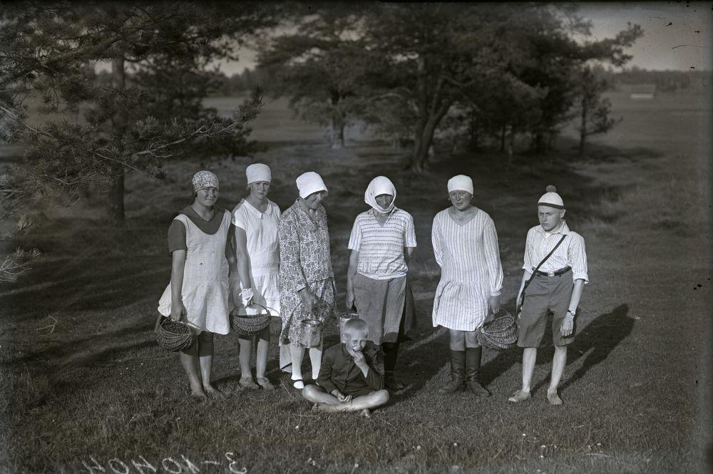 Fotol naised ja noorukid korvidega metsa veerel.