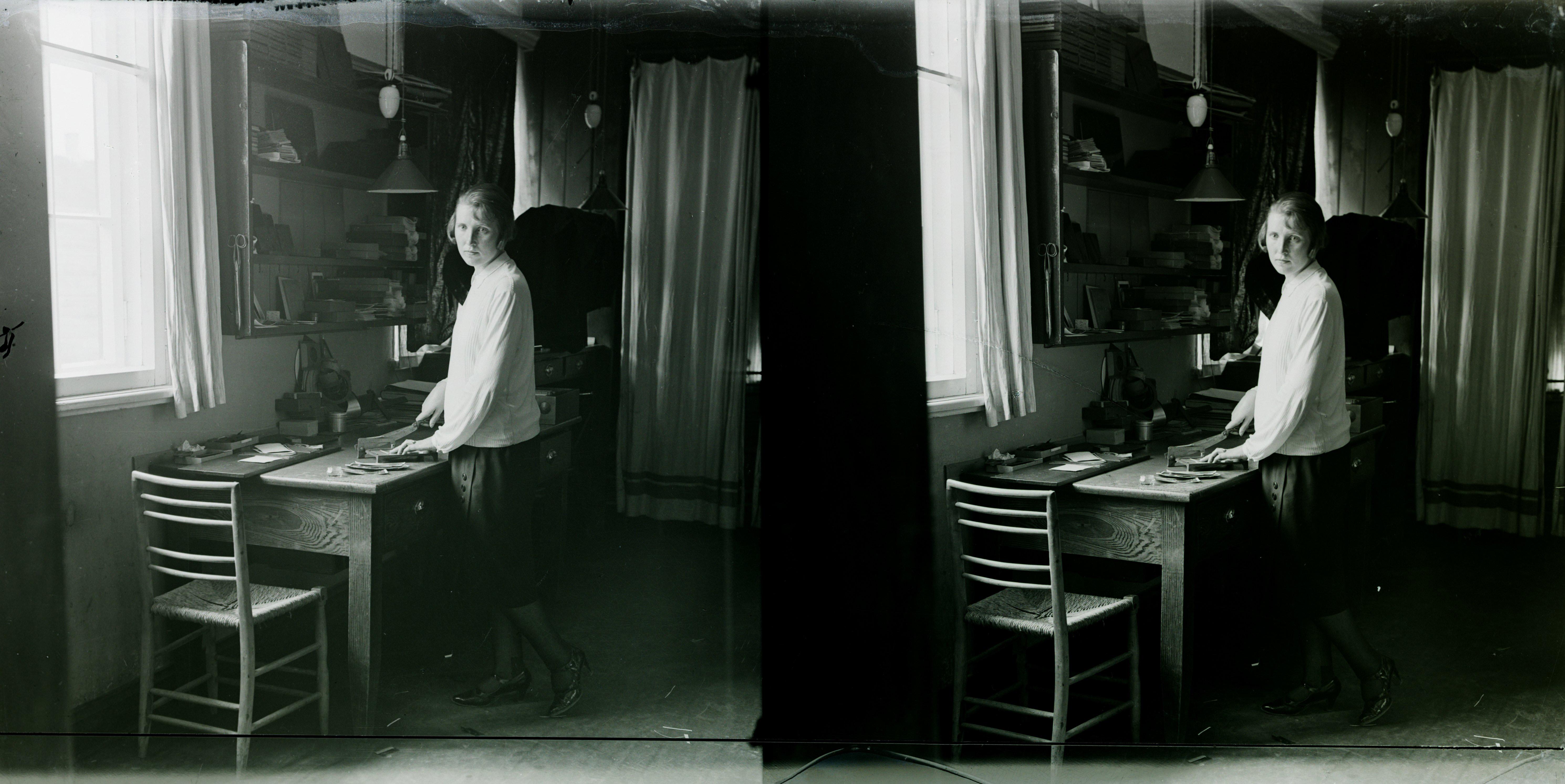 Posti ja Koidu tänava nurgal asunud Jaan Rieti fotoateljee sisevaade, esiplaanil ateljeetööline, laual fotode ja negatiivide viimistlusvahendid, tagaplaanil akna ääres laual negatiivide retuššimispult, u 1920–30. Jaan Riet, stereonegatiiv, EFA.4-6569