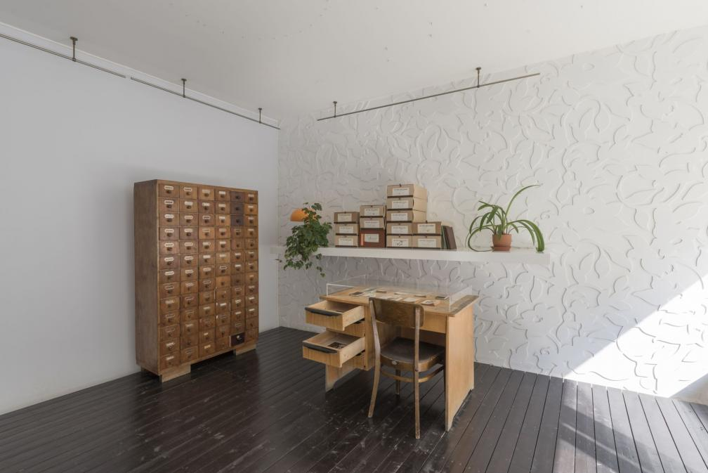 """Näituse """"Benita Labi: Splendid loneliness"""" vaade - arhiivikapp, kirjutuslaud, tool ja riiul arhiivikarpidega."""