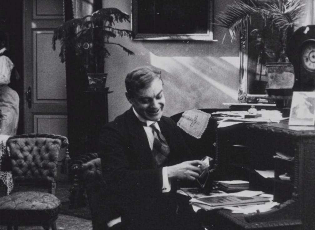"""Kaader filmist """"Laenatud naene"""". Mees istub kirjutuslaua taga."""