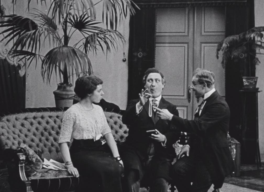 """Kaader filmist """"Laenatud naene"""". Toas diivanil istuvad naine ja kaks meest ning vestlevad."""