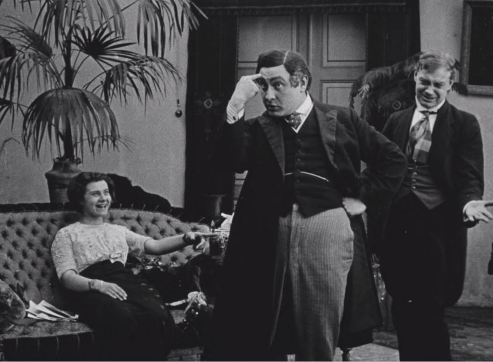 """Kaader filmist """"Laenatud naene"""". Naine istub diivanil ja naerab. Kaks meest seisavad."""