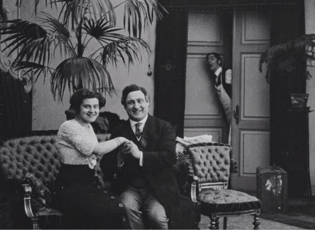 """Kaader filmist """"Laenatud naene"""". Naine ja mees istuvad käsikäes naeratades diivanil, ukse vahelt vaatab teener."""
