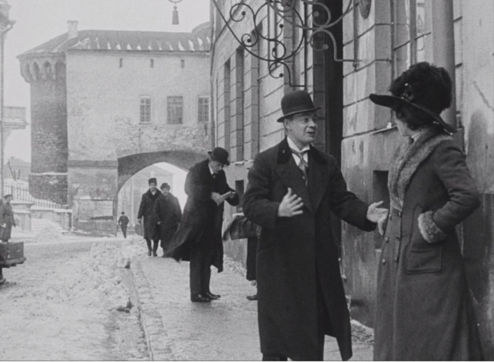 """Kaader filmist """"Laenatud naene"""". Talvisel linnatänaval maja ääres kõnniteel vestlevad naine ja mees."""
