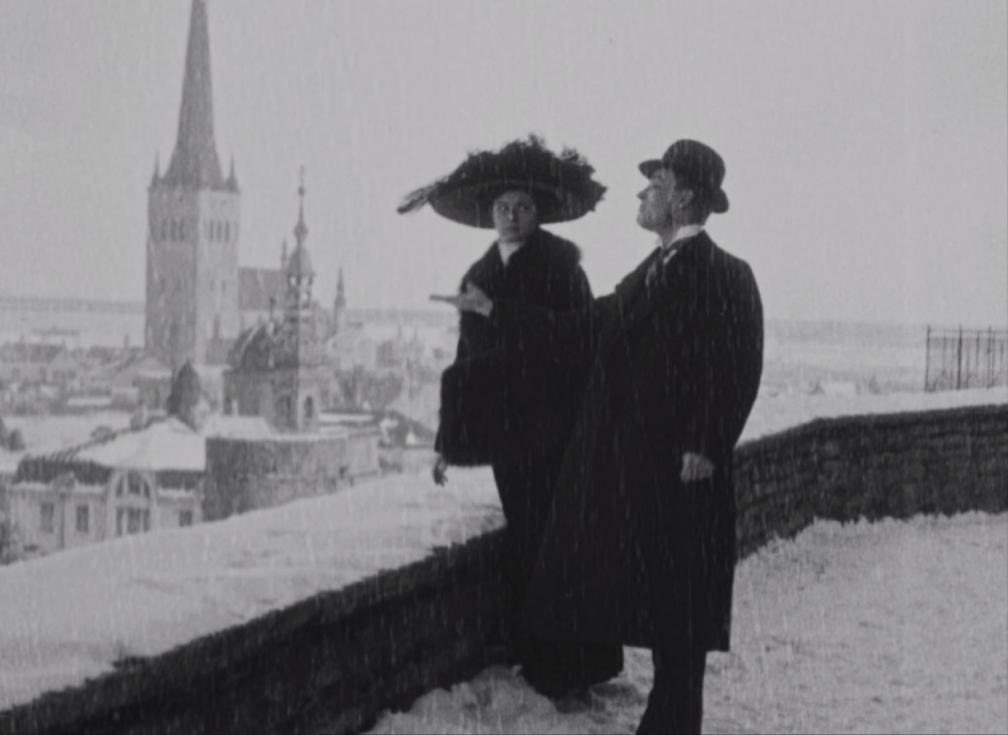 """Kaader filmist """"Laenatud naene"""". Tallina vanalinna vaateplatvormil seisavad naine ja mees. Taamal paistab Oleviste torn."""