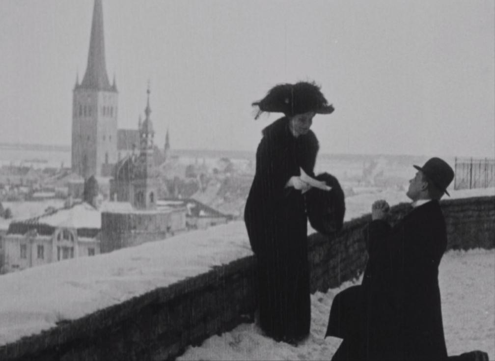 """Kaader filmist """"Laenatud naene"""". Tallinna vanalinna vaateplatvormil seisab kübaraga naine, tema ees põlvitab mees."""