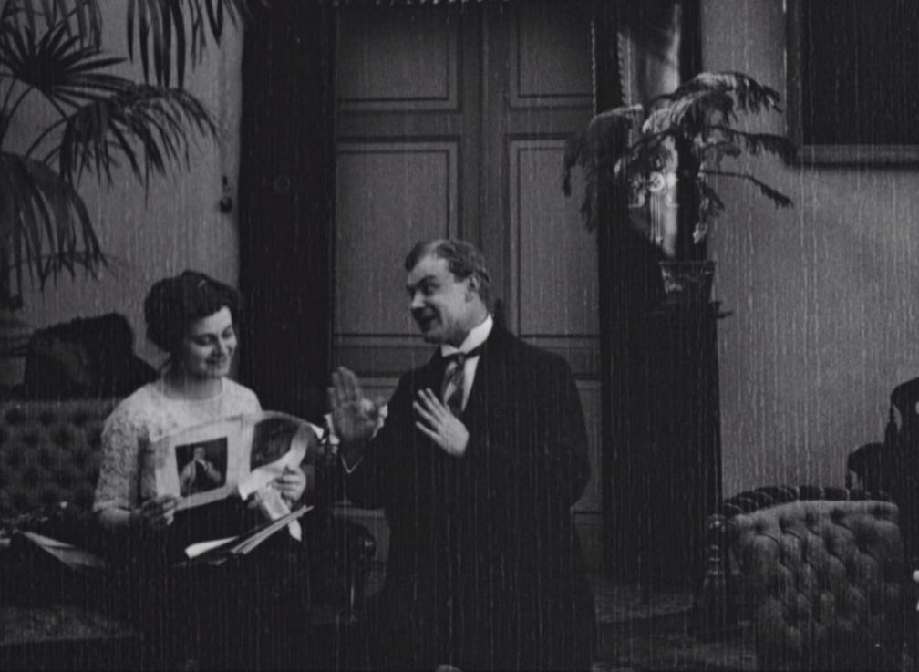 """Kaader filmist """"Laenatud naene"""". Toas vestlevad naine ja mees."""