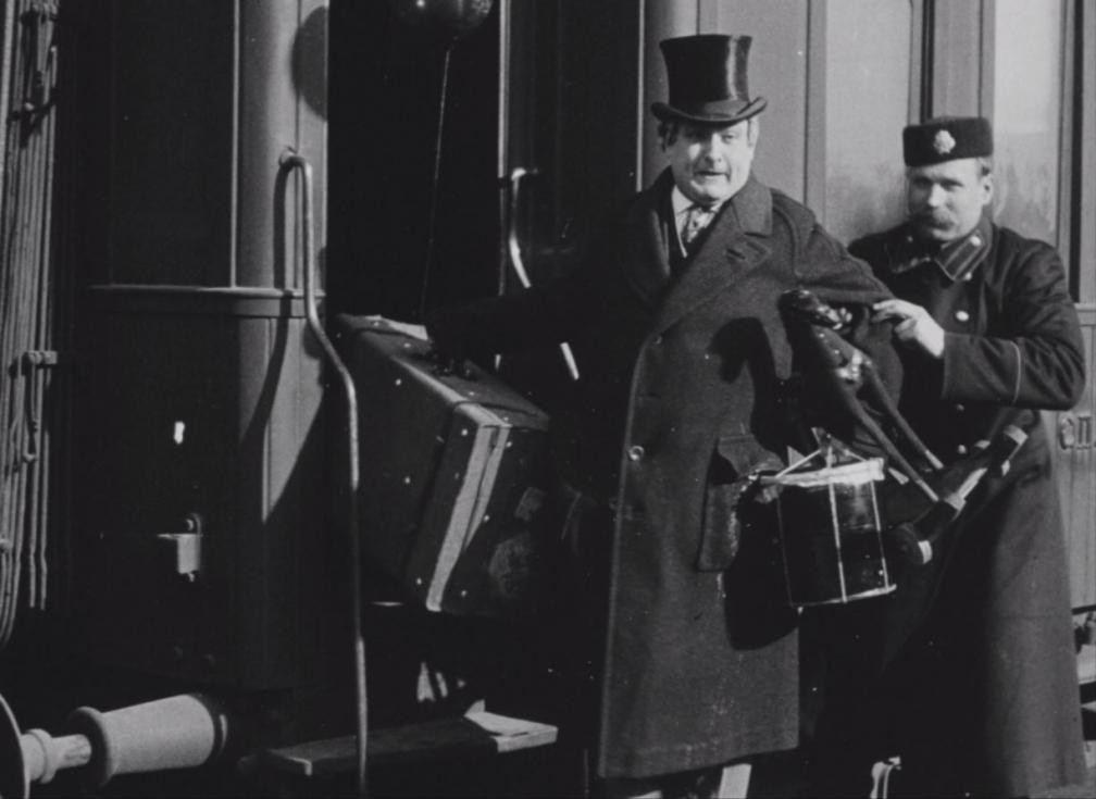 """Kaader filmist """"Laenatud naene"""". Kaks talvepalitus ja univormis meest tassivad kohvreid."""