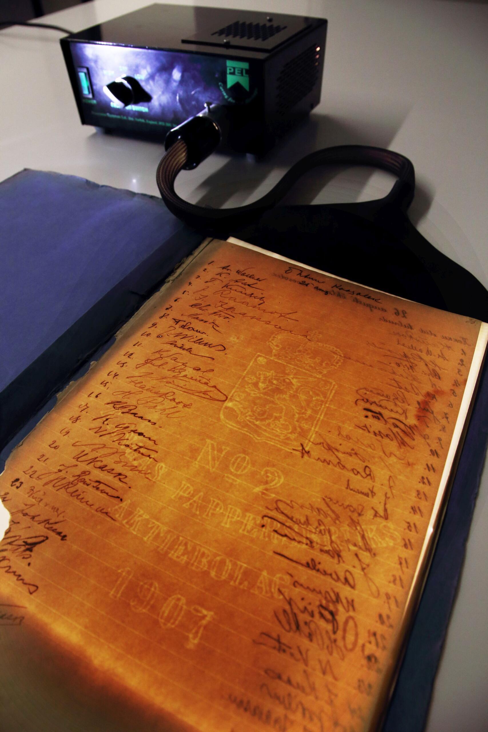 Valgusleht paljastamas NOORA püsinäituse objekti sisemaailma. Vesimärk kõneleb, et see paber on valmistatud Soomes Kangase paberivabrikus